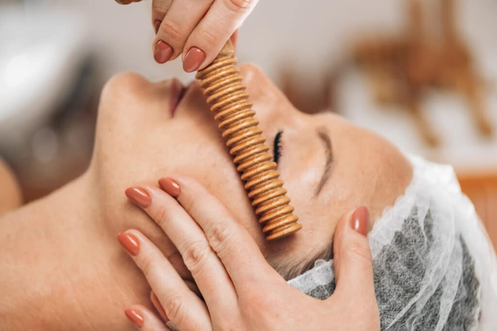 Face Massage. Anti-aging madero therapy face treatment with ribbed wooden stick at cosmetology center