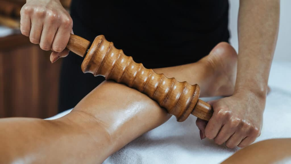 Madero therapy back thigh muscle massage with wooden rolling pin or battledore